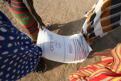 Displaced women carry a sack of food (file photo).