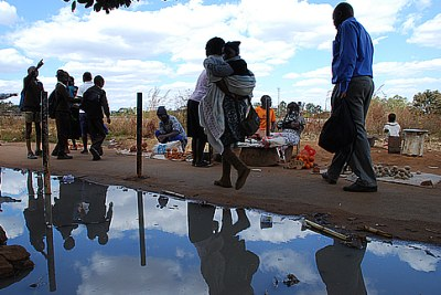 Residents of Kuwadzana in Harare walk past raw sewage.