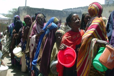 Displaced people wait to be given food during a distribution organised by the UN World Food Programme, USAID and other local and international NGOs in Somalia.
