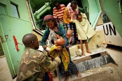 A Somali woman hands her severely malnourished child to a medical officer of the African Union Mission in Somalia (file photo).