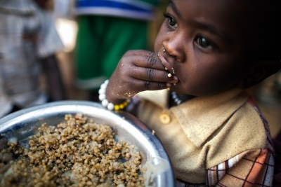 A child has a meal at a food distribution centre in the Rwanda camp for internally displaced persons (IDPs), near Tawila, North Darfur. More than 8,000 women and children living in the camp benefit from nutrition programmes run by the World Food Programme (WFP).