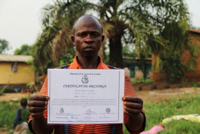Saa Sabas Temessadouno, 48, displays his Ebola-free certificate after surviving the disease.