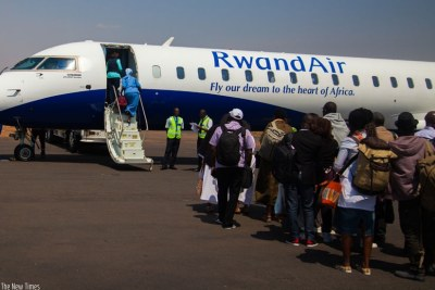 Passengers board a RwandAir plane heading to Cotonou at Kigali International Airport.