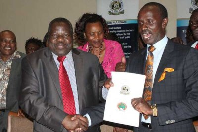 Knut chairman Mudzo Nzili (left) and Secretary-General Wilson Sossion display collective bargaining agreement that was signed between the union and the Teachers Service Commission (TSC) on October 25, 2016.