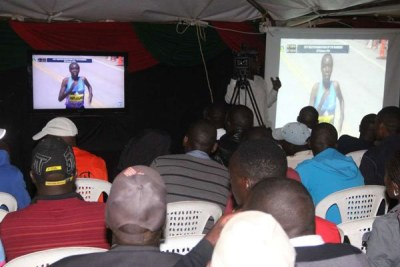 Athletics fans watch the Boston Marathon on a Television on April 17, 2017. Geoffrey Kirui and Edna Kiplagat won the men's and women's race respectively.