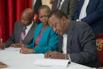 President Uhuru Kenyatta signs reply documents on the presidential election petition at the State House.
