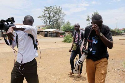 Journalists react after they were teargassed by anti-riot police who did not want to be filmed during a demonstration in Kisumu on October 13, 2017 (file photo).