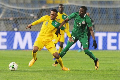 Amavubi's Ali Niyonzima (left) holds off a Nigerian player during their Group C match at Grand Stade de Tanger.