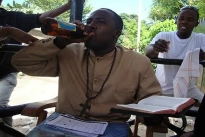 The self-styled prophet holds a Bible while drinking from a beer bottle.