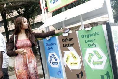 A woman deposits trash in an eco-bin within Nairobi's Central Business District.