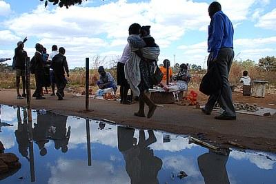 Residents of Kuwadzana in Harare walk past raw sewage.