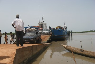 A man watches as vehicles, people are unloading from the Senegambia ferry - bateau - boat - frontiere - border - fleuve river