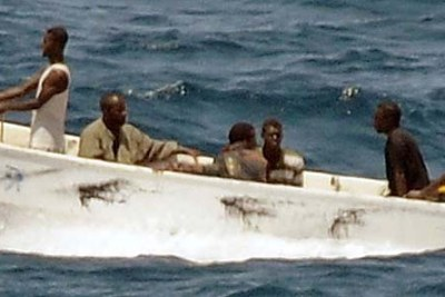 Pirates travel to shore while under observation by a U.S. Navy ship.