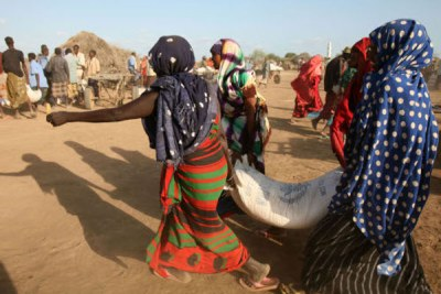 Displaced women carry a sack of food during a UN World Food Programme distribution in Jowhar, Somalia, September 2007.