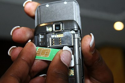 A mobile phone user inserts a SIM card into a phone. Kenya has launched a campaign to register all mobile phone subscribers.