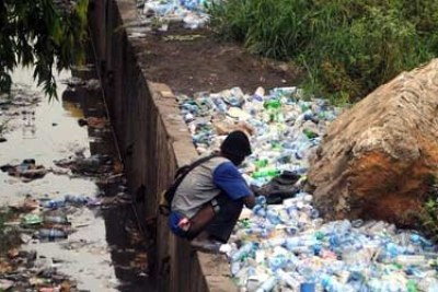 A man defecates in a canal in Lagos State, Nigerian.