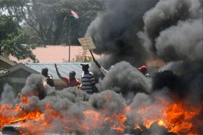 Post-election violence (file photo): Protesters taunt riot police behind a burning roadblock during clashes disputing the re-election of President Mwai Kibaki.