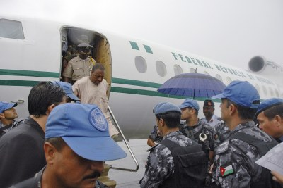 Former Liberian President Charles Taylor alights from the Nigerian government plane into the waiting handcuffs of United Nations Peacekeepers. March, 2006.