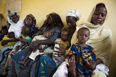 Des mères avec leurs bébés attendent dans un centre de santé maternel à Niamey au Niger, où le PAM distribue des rations alimentaires.
