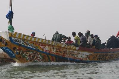 Transfert de poissons entre deux pirogues de pêcheurs rencontrées sur la route de la brèche à Saint-Louis du Sénégal