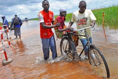 Des habitants de Soroti aident une vielle femme à traverser le pont inondé de Awoja.