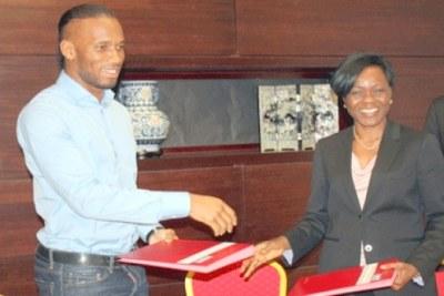 Didier Drogba échangeant le paraphé avec Kaba Nialé, ministre auprès du Premier ministre chargée de l'Economie et des Finances