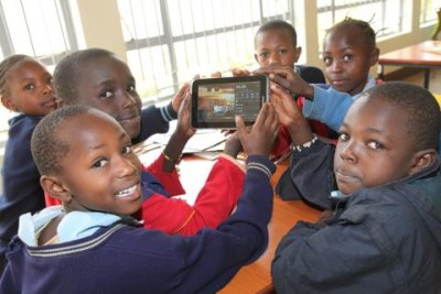 School children hold up one of the Samsung tablets used at the library.
