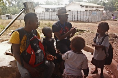 Chernor Bah talks with a widower whose wife died from Ebola and he now takes care of his three children alone