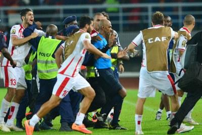 L'arbitre Rajindraparsad Seechurn est escorté hors du terrain par la police alors que les joueurs tunisiens le confrontent, indigné par sa décision d'accorder une pénalité à la Guinée équatoriale.