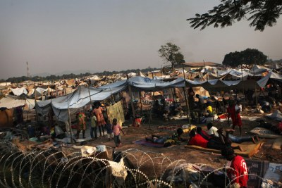 Des enfants et des adultes déplacés s'abritent à l'extérieur d'une clôture de barbelés, dans un camp mis en place derrière l'aéroport international Mpoko de Bangui, en République centrafricaine (RCA). - (Archive)
