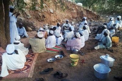 Men from Leeba gather under a tree to read the Koran, pray to God to avoid any Antonovs bombing the area.
