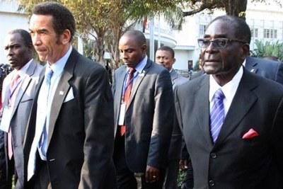 Ian Khama, président du Botswana (à gauche), marchant aux côtés de son homologue du Zimbabwe, Robert Mugabe, (à droite).
