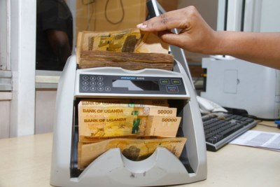 A person counting Ugandan shillings (file photo).