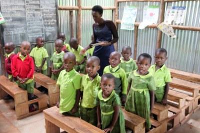 Bridge International Academies Kasokoso teacher Miriam Nambya attends to nursery kids in class November 7.