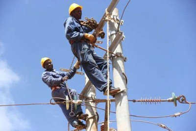Kenya Power workers fix electricity poles (file photo).