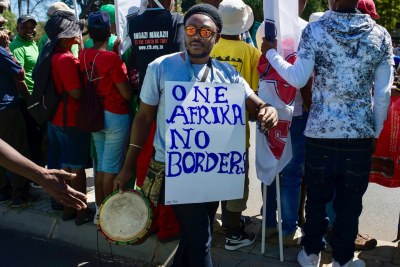 A man with a sign calling for the abolition of borders on the African continent is seen during the anti-xenophobia march in Johannesburg (file photo).