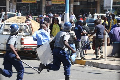 Riot cops chase MDC-T supporters in Harare.