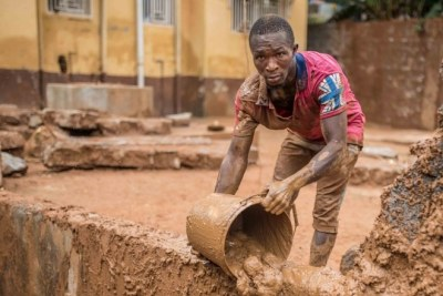 Five days after the mudslide in Sierra Leone, a resident is still moving mud from his home.