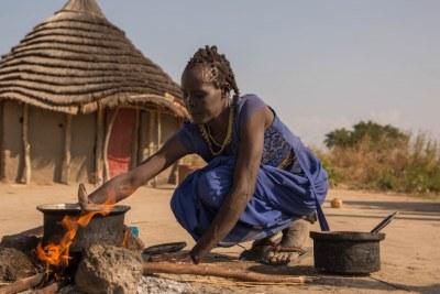 Nyanciech Hiieu agite un mince bouillon de légumes dans une casserole au-dessus du feu.