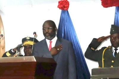 President Weah poses for the playing of the national anthem.