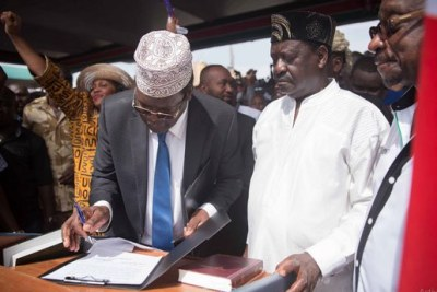 Miguna Miguna (left) puts pen to paper during Raila Odinga's swearing in as the people's president at Uhuru Park, Nairobi on January 30.