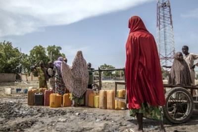 Women and children collect water in Mafa IDP camp, Borno state, north-east Nigeria (file photo).