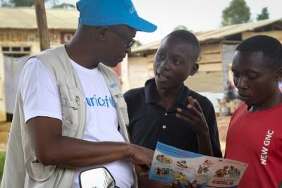 Le 12 septembre 2018 à Beni, un membre du personnel de l'UNICEF discute du meilleur moyen de se protéger contrel' Ebola, lors d'une conversation avec des jeunes vivant à Beni, en République démocratique du Congo, après une récente épidémie d'Ebola.