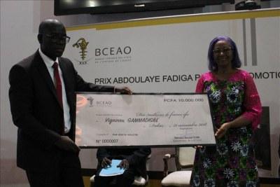 Le Togolais Vigninou GAMMADIGBE, lauréat du Prix Abdoulaye Fadiga pour la Promotion de la recherche économique 2018, recevant son chèque des mains de Mme Marie Elisabeth Viviane Zunon Kippre, première femme cadre a la BCEAO.