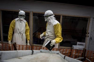 Un agent de santé rassemble une bible pour donner à l'un des patients confirmés Ebola dans un centre de traitement Ebola soutenu par MSF