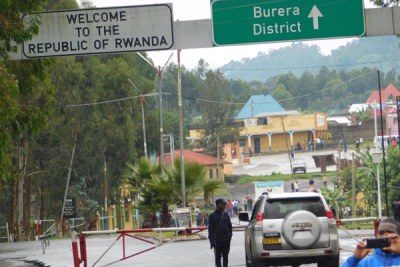 A Rwandan security officer inspects a vehicle from the Ugandan side at Cyanika border post.