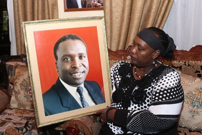 Sylvia Toroitich Moi holds a portrait of her late husband, Jonathan Toroitich, at their home in Kabimoi Farm in Eldama Ravine.