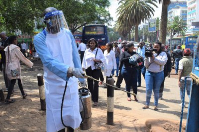 A ministry of health official fumigates a Nairobi street as part of measures to combat coronavirus (file photo).
