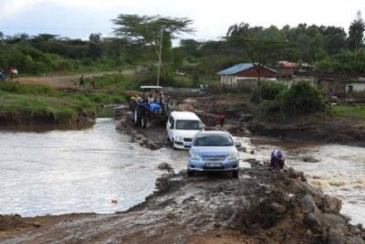 Les piétons et les automobilistes sont représentés sur une route endommagée par les inondations à Mulot dans la circonscription de Narok South le 4 mai 2020.