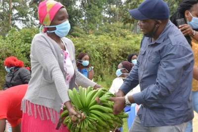 Ahadi Kenya Trust Director Stanley Kamau (right) donates food to a resident of Murang'a rendered jobless by Covid-19.